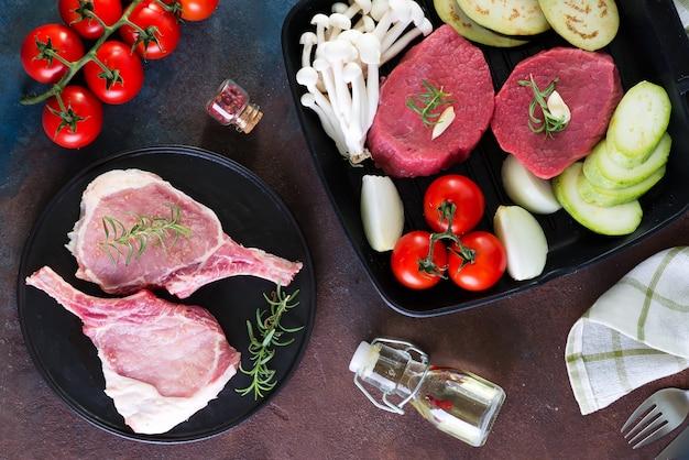 Carne e verdure fresche crude degli ingredienti naturali per la cottura della cena su un fondo di pietra scuro.