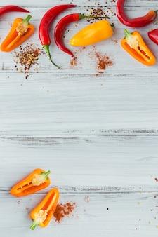 Peperoncino rosso organico fresco crudo e spezie assortite su superficie di legno bianca