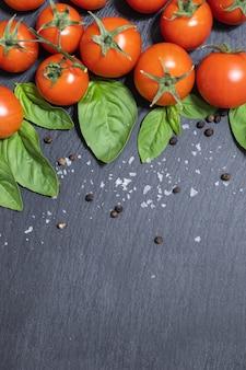 Pomodorini rossi freschi crudi su fondo scuro con basilico e aglio