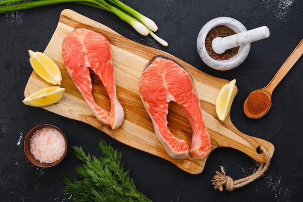 Bistecca di color salmone fresca cruda sul tagliere di legno