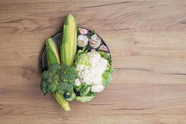 Verdure fresche crude su un piatto su una vista superiore del fondo della tavola in legno.