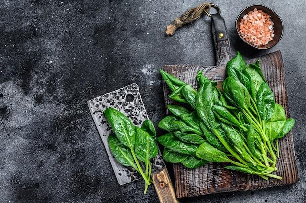 Foglie di spinaci giovani freschi crudi su un tagliere di legno