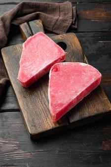 Set di filetti di tonno crudo congelato, su tagliere di legno, su vecchio tavolo di legno scuro