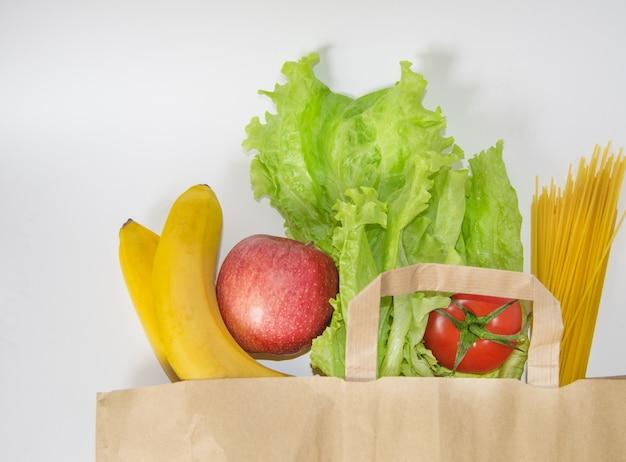 Frutta e verdura crude, pasta srotolata da un sacco di carta su un muro bianco, concetti di shopping, consegna di cibo