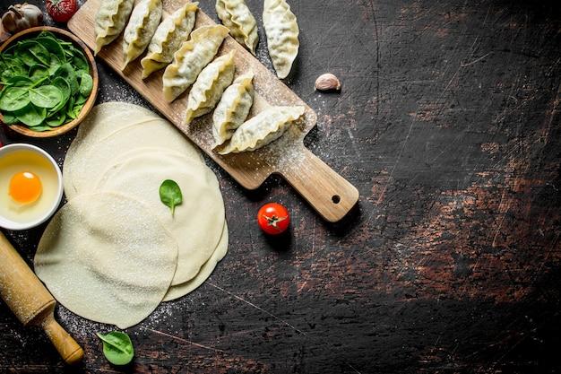 Gnocchi di gedza crudi. preparazione gedza gedza con spinaci sul tavolo di legno scuro