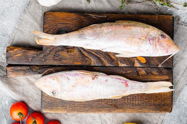 Pesce intero fresco di capra crudo, con ingredienti ed erbe aromatiche, su sfondo di tavolo in pietra grigia, vista dall'alto piatta