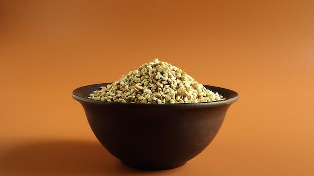 Grano saraceno verde crudo in un piatto di argilla marrone su uno spazio marrone. concetto di cibo biologico vegano.