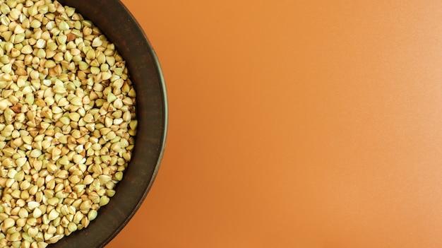 Grano saraceno verde crudo in un piatto di argilla marrone su uno spazio marrone