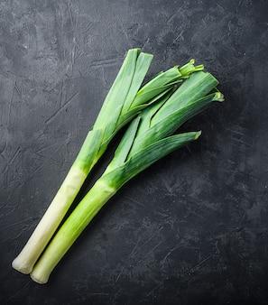 Porri organici verdi crudi sul nero