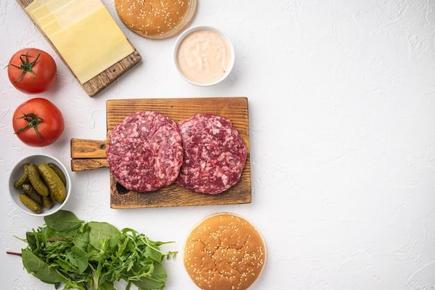 Cotolette e condimenti della bistecca dell'hamburger della carne macinata cruda della carne di manzo con i panini messi, su fondo di pietra bianca, disposizione piana di vista superiore, con lo spazio della copia per testo