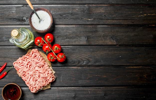 Carne di manzo macinata cruda con pomodori e spezie. su uno sfondo di legno.