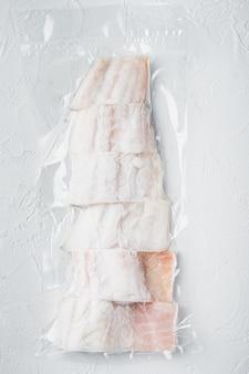 Pesce crudo eglefino senza pelle, confezionato sottovuoto in plastica, sul tavolo bianco, vista dall'alto