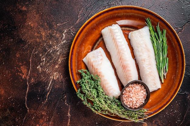 Filetto di filetto di lombo di eglefino crudo su piatto rustico con timo e sale. sfondo scuro. vista dall'alto. copia spazio.