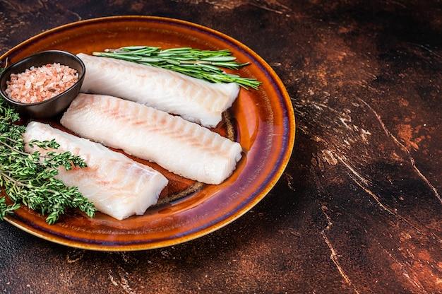 Pesce crudo di filetto di lonza di eglefino su piatto rustico con timo e sale. sfondo scuro. vista dall'alto. copia spazio.