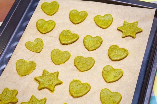 Biscotti crudi fatti in casa con tè verde matcha a forma di stella e a forma di cuore su teglia