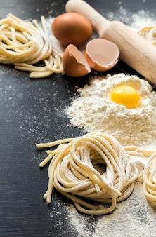 Pasta fatta in casa cruda con ingredienti su sfondo nero. messa a fuoco selettiva.