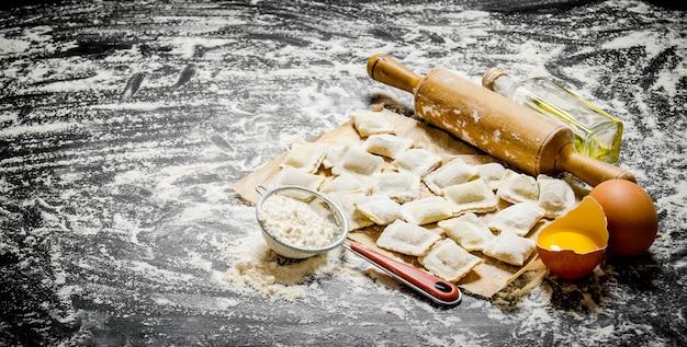Ravioli fatti in casa crudi con uovo, farina e mattarello.