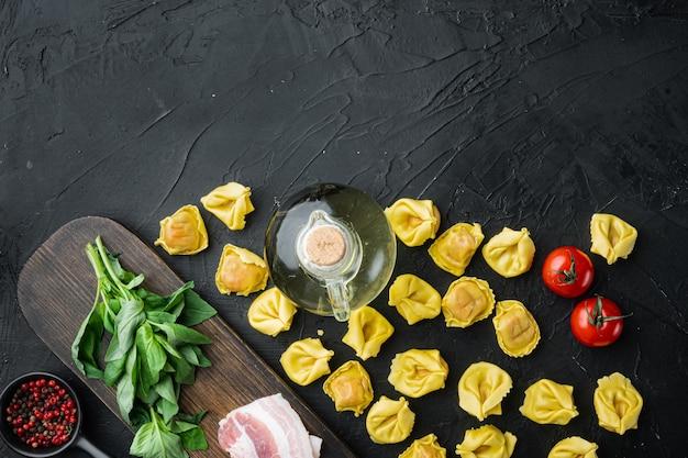 Tortellini fatti in casa crudi con prosciutto crudo impostato, sulla tavola nera, vista dall'alto laici piatta