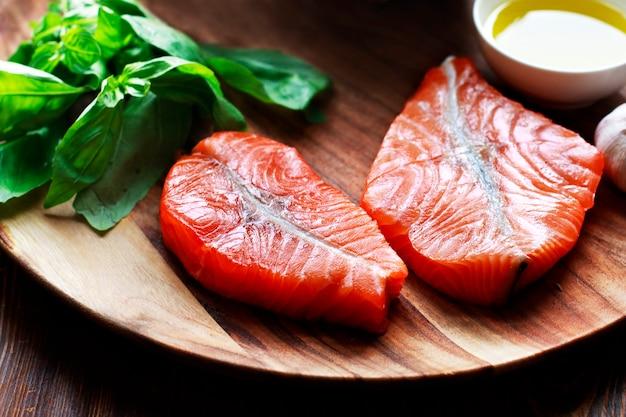 Bistecche di salmone crudo megattere, fondo di legno rustico, sopra la vista. filetto con ingredienti freschi per una gustosa cottura e padella. vista dall'alto. concetto di cibo sano e dietetico.
