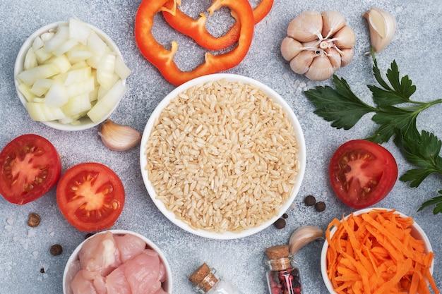 Materie prime per cucinare pilaf, riso integrale e filetto di pollo, carote grattugiate e cipolle tritate, erbe aromatiche e spezie. tavolo grigio, vista dall'alto.