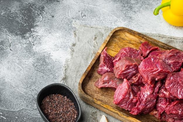 Materie prime per il gulasch. carne di manzo tritata cruda fresca con peperone dolce, sul tavolo di pietra grigia