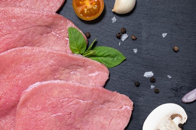 Materie prime a fette di manzo rosso erbe pomodori aglio sale e pepe