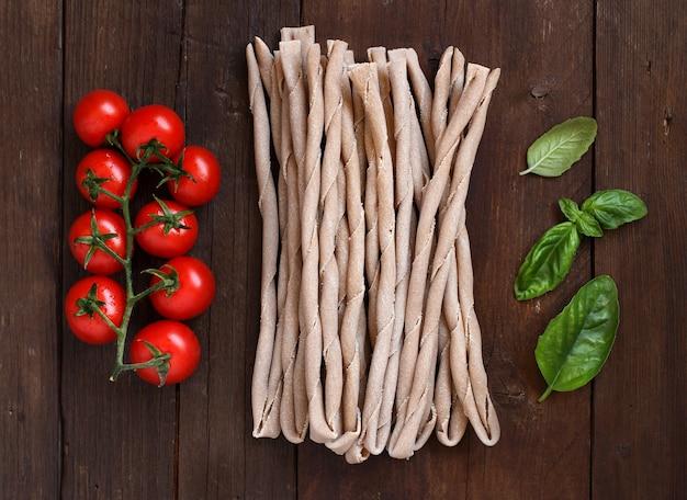 Pasta italiana cruda, basilico e verdure su fondo di legno
