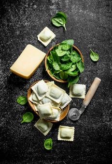 Ravioli italiani crudi con formaggio e spinaci sul tavolo rustico scuro.