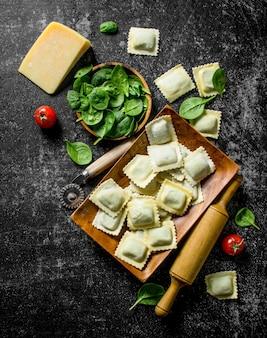 Ravioli italiani crudi con formaggio e spinaci. sul tavolo rustico scuro