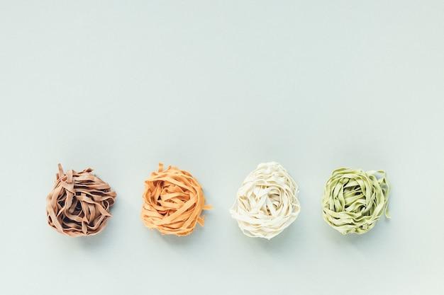 Pasta italiana cruda di tagliatelle su sfondo chiaro