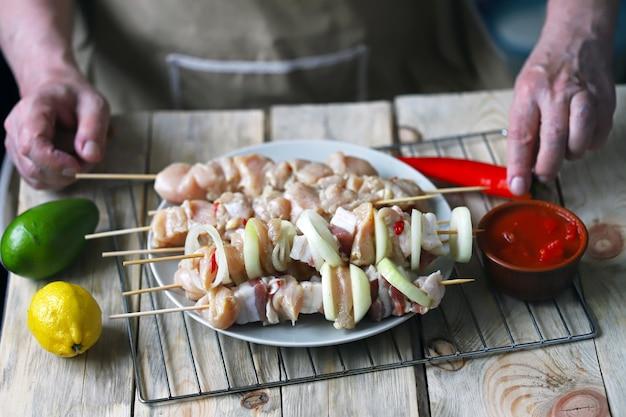 Gli spiedini crudi su bastoncini di legno sono preparati dallo chef.