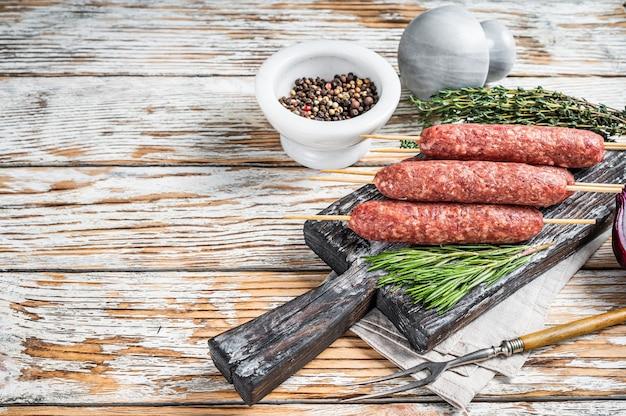 Salsicce di carne crude kofta o lula kebab su spiedini con erbe aromatiche. fondo in legno scuro. vista dall'alto. copia spazio.