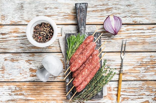 Salsicce crude di carne di kofta o lula kebab su spiedini con erbe aromatiche. fondo in legno scuro. vista dall'alto.