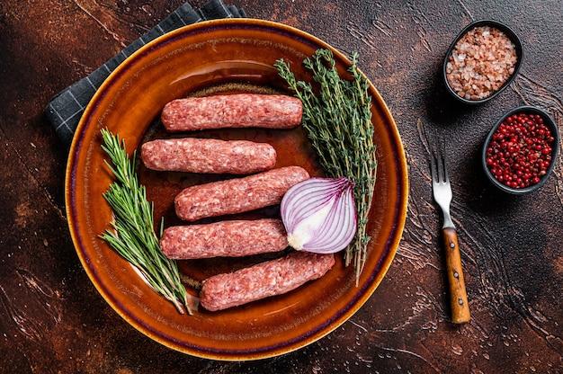 Kofta cruda carne kebab salsicce su un piatto con erbe aromatiche. sfondo scuro. vista dall'alto.