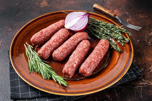 Salsicce crude di spiedini di carne kofta su un piatto con erbe aromatiche. sfondo scuro. vista dall'alto.