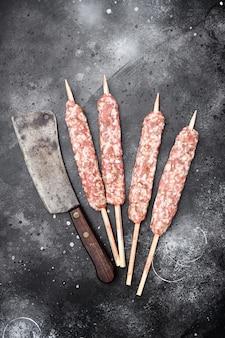 Set di salsicce di spiedini di carne kofta cruda, su sfondo nero tavolo in pietra scura, vista dall'alto piatta