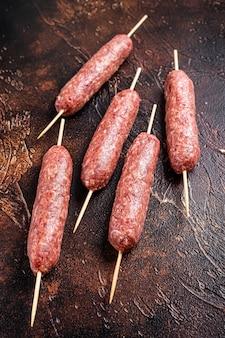 Salsicce crude di spiedini di carne kofta su spiedini. sfondo scuro. vista dall'alto.