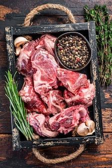 Carne di agnello o capra cruda tagliata a dadini per lo stufato con l'osso legno scuro