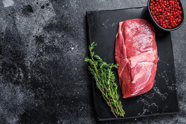 Bistecca di coscia di carne di agnello cruda su una tavola di pietra