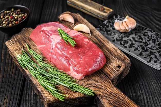 Bistecca di controfiletto di carne di agnello cruda su un tagliere di legno