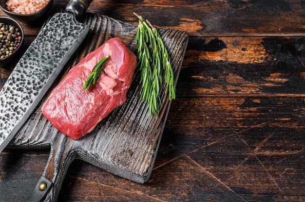 Bistecca di carne di agnello cruda su un tagliere di legno con erbe aromatiche