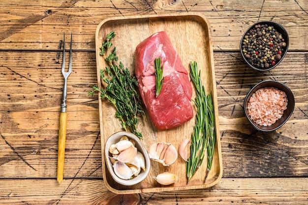Bistecca di carne di agnello cruda in un vassoio di legno con erbe aromatiche
