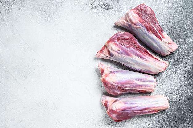 Carne di stinco di agnello crudo sul tavolo di pietra. tavolo bianco. vista dall'alto. copia spazio.
