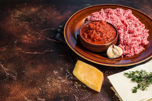 Ingredienti e prodotti crudi della lasagna per pasta sfondo scuro. vista dall'alto. copia spazio.