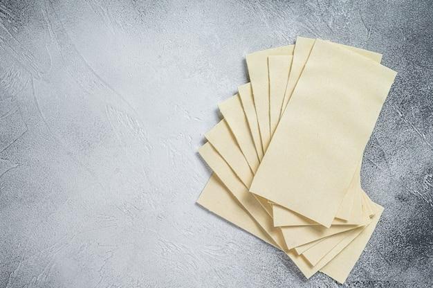 Fogli di lasagne crude impilati su un tavolo da cucina. sfondo bianco. vista dall'alto. copia spazio.