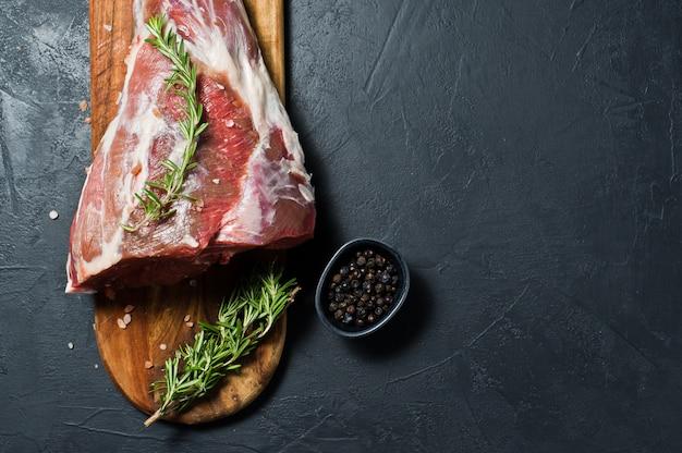 Un cosciotto d'agnello crudo su un tagliere di legno. rosmarino, timo, pepe nero.