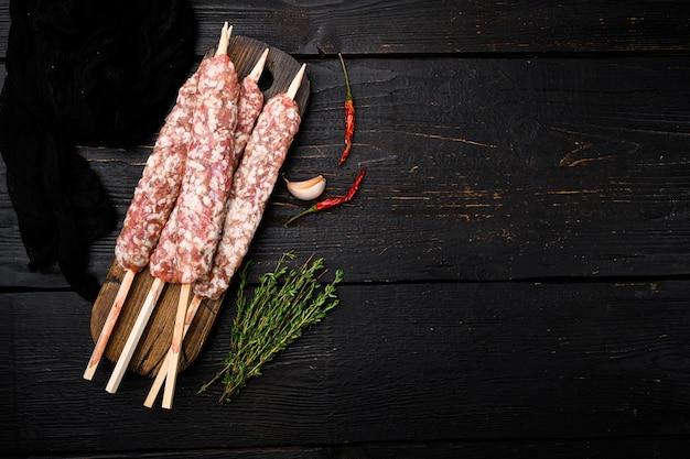 Lula kebab crudo, carne macinata lyulya-kebab, shish kebab pronto da cucinare, su sfondo tavolo in legno nero, vista dall'alto piatta, con copia spazio per il testo