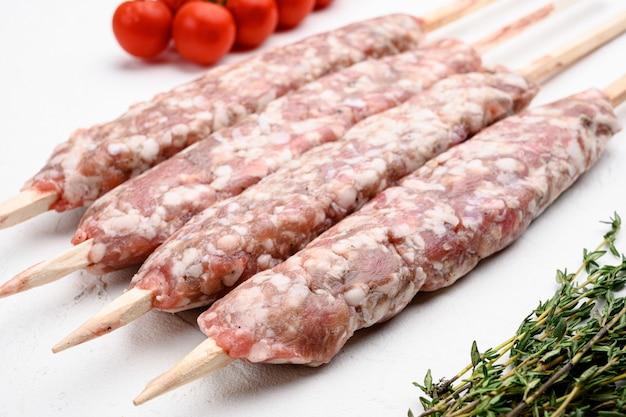 Kebab crudo di lula, carne macinata di lyulya-kebab, shish kebab pronto da cucinare insieme, con gli ingredienti della griglia, sul fondo di pietra bianco della tavola
