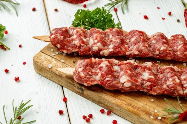 Kebab crudo del lula sugli spiedi con le spezie sul bordo di legno