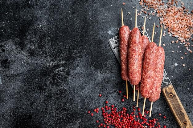 Spiedini di lula o kofta crudi su una mannaia da macellaio con sale e pepe. sfondo nero. vista dall'alto. copia spazio.